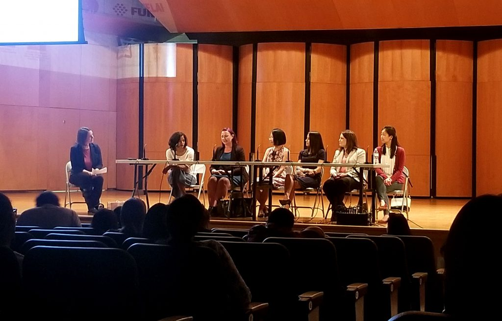 Seven women on stage. 6 panelists and 1 moderator.
